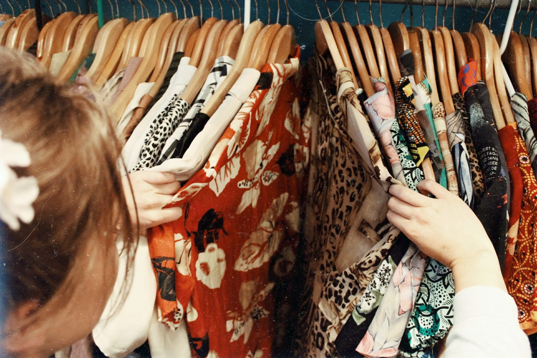 Young woman shopping for clothes at a clothing store or thrift store