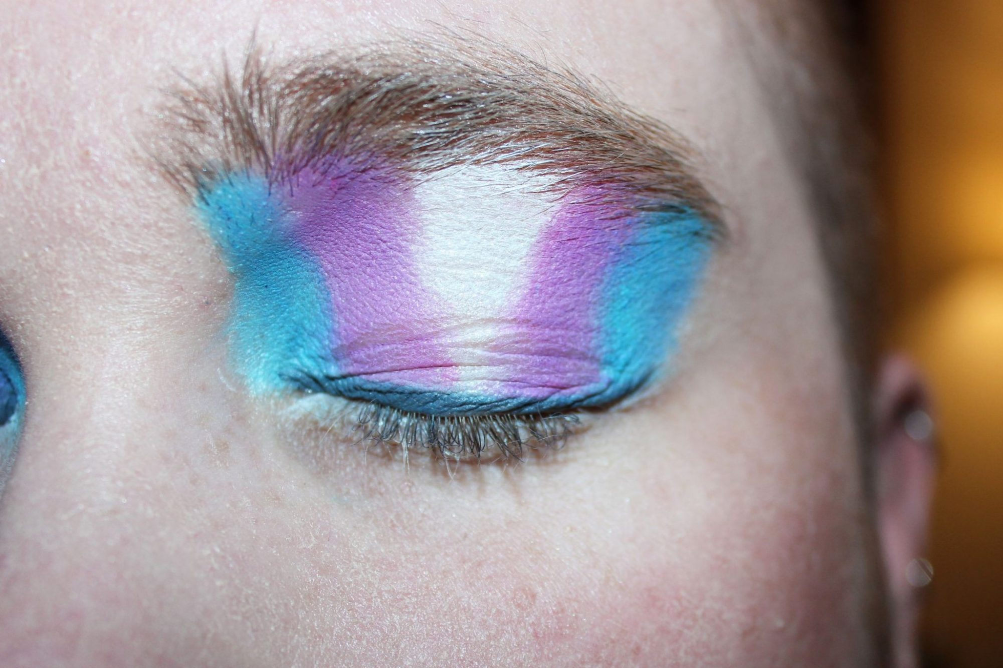 Photo of a trans person with eyeshadow that is the color of the transgender pride flag